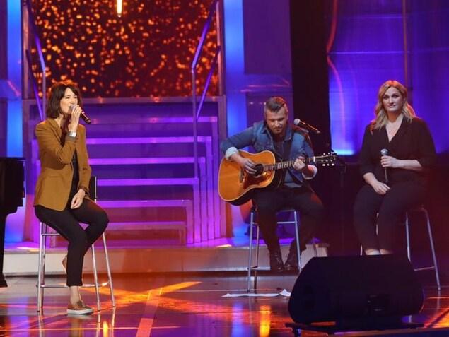Un pianiste, une chanteuse sur un tabouret, un guitariste et une choriste sur scène.