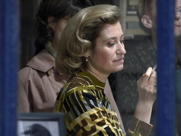 Une femme, dans une librairie, entourée de gens attentifs, fume une cigarette.