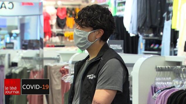 Un commis de magasin avec un masque.