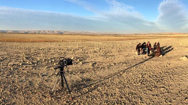 Un groupe d'hommes dans le désert. Une caméra les filme au loin.