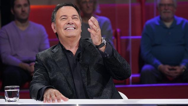L'homme est assis dans le studio et sourit en levant la main.