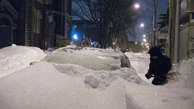 Un homme déneigeant sa voiture près de l'église St-Charles