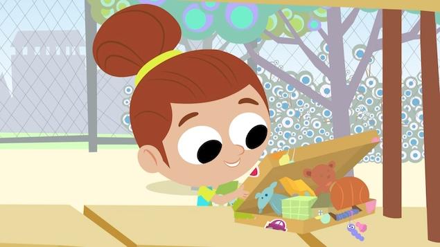 Amala ouvre une boîte pleine de jouets. Elle sourit.