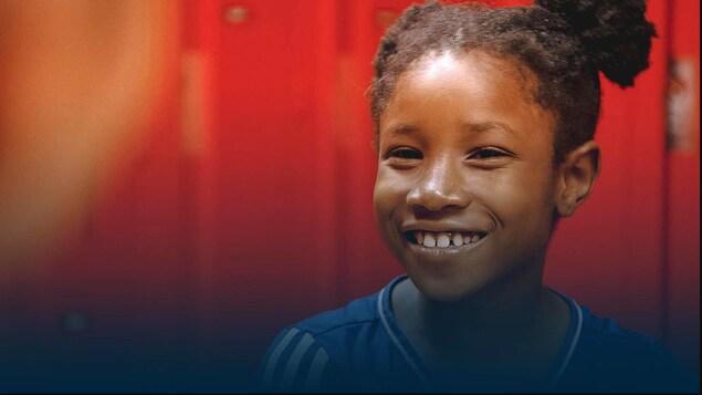 La jeune fille sourit, elle porte une tenue de gymnastique