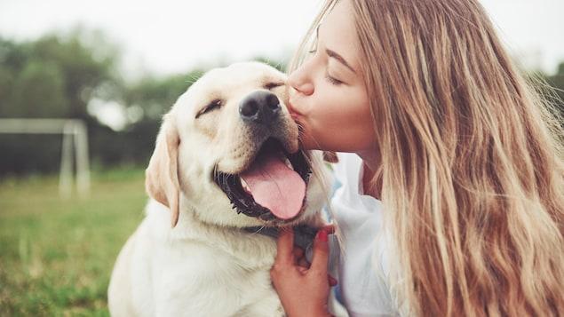 Une jeune ado fait un bisou à son labrador