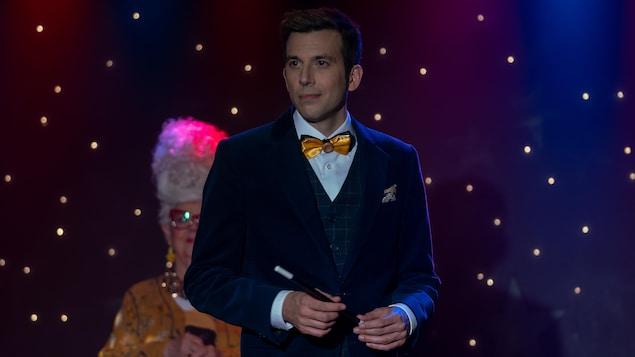 Daniel Coutu est sur scène avec sa baguette magique à la main.