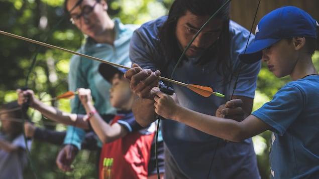 Des animateurs donnent une activité de tir à l'arc aux enfants