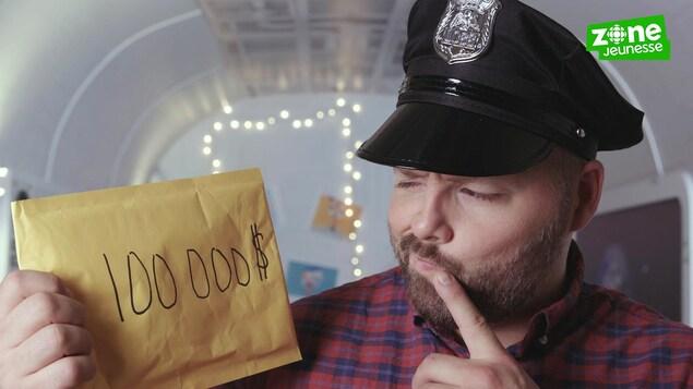 Il regarde une enveloppe brune avec 100000 $ écrit dessus
