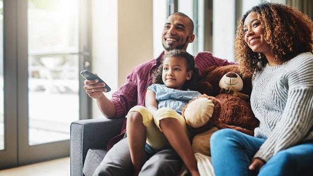 On voit un papa, une maman et leur fillette assis dans un canapé devant la télé en souriant