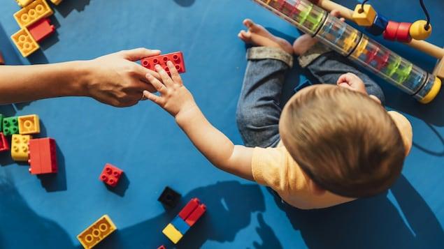 Un bébé, vu de haut, joue avec des blocs LEGO.