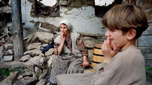 Des Albanais devant leur maison détruite par des combats en 1998