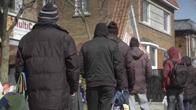 Des personnes font la file à l'extérieur pour avoir accès à de l'aide alimentaire.