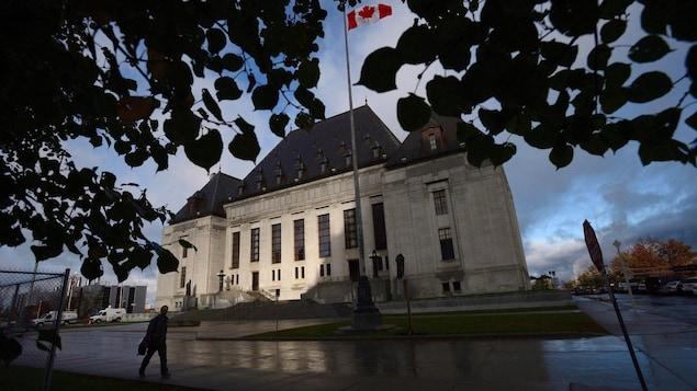 Un homme marche devant la Cour suprême du Canada.