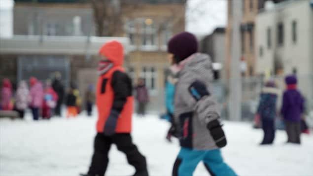 Des enfants dans une cour d'école l'hiver.
