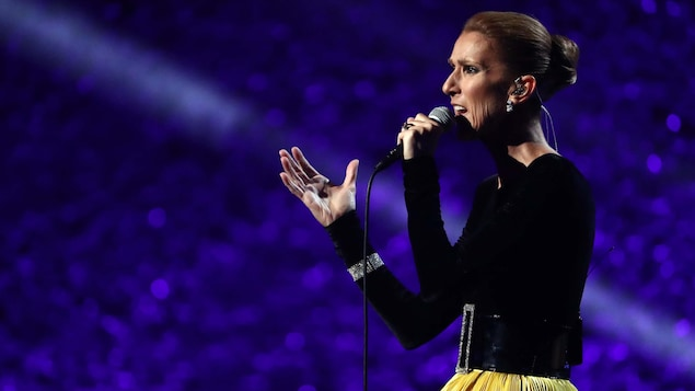 Céline Dion, micro à la main, chante sur scène.