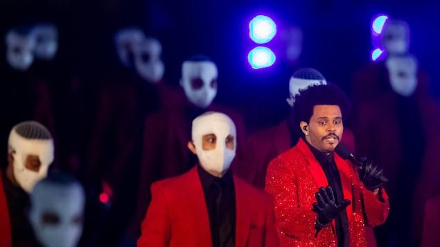 The Weekend chante sur scène avec des danseurs masqués.