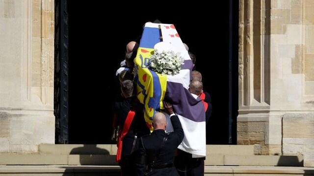 Des hommes transportent le cercueil, recouvert d'un étendard et d'un bouquet de fleurs.