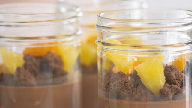 Deux pots de verre avec un crémeux au chocolat et au rooibos avec un crumble au chocolat et des fruits.