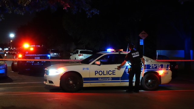 Un policier qui ouvre la portière d'une auto-patrouille.
