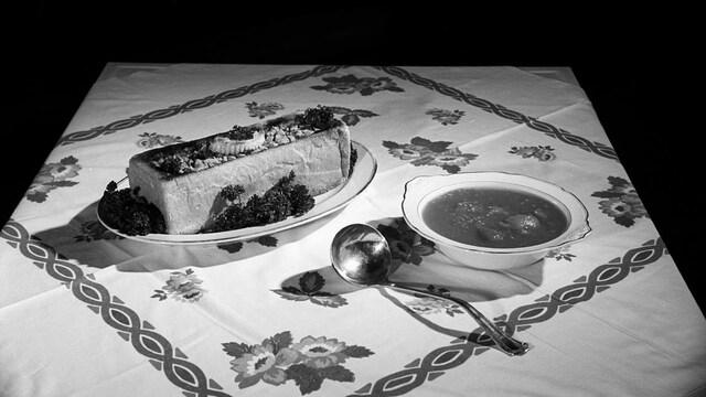 Présentation d'un pain farci et d'une soupière sur une table avec une nappe soignée.