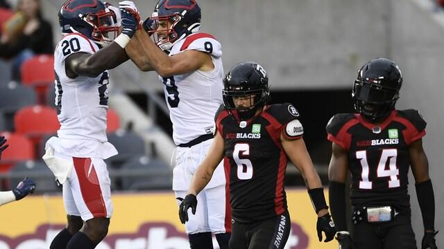 Jake Wieneke et Jeshrun Antwi sautent ensemble en se tenant les mains devant deux joueurs de l'équipe du Rouge et Noir Antoine Pruneau et Abdul Kanneh.