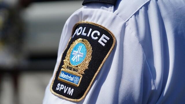 Gros plan sur un badge du SPVM sur la manche d'une chemise.