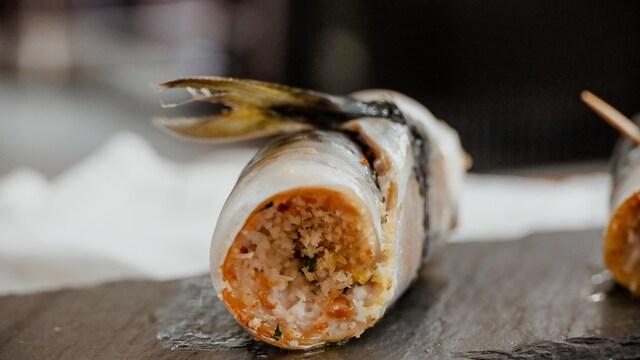 Un rouleau de poisson est sur une planche de pierre.