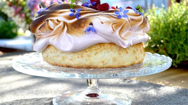 Beau gâteau décoré de meringue, de framboises et des fleurs