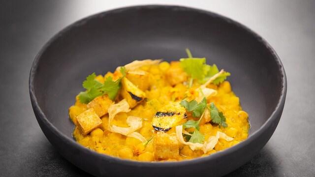Ragoût de pois chiches d'inspiration indienne dans un bol rond en terre cuite.