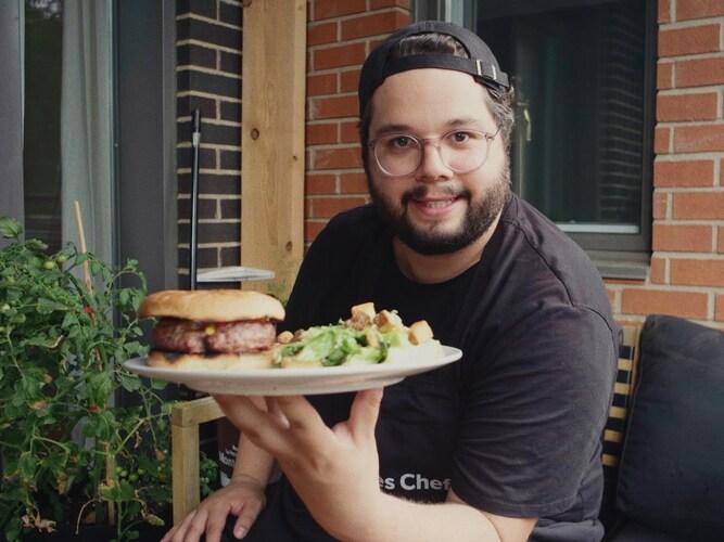 Matthieu Pepper tenant une assiette contenant son fameux Pepper Burger accompagné d'une salade césar.