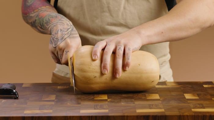 Une courge musquée est déposée sur une planche à couper, et deux mains la manipule pour la couper.