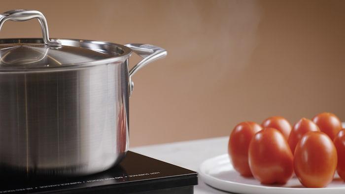 Un chaudron est déposé sur une plaque de cuisson. À sa droite, des tomates sont déposées dans une assiette.
