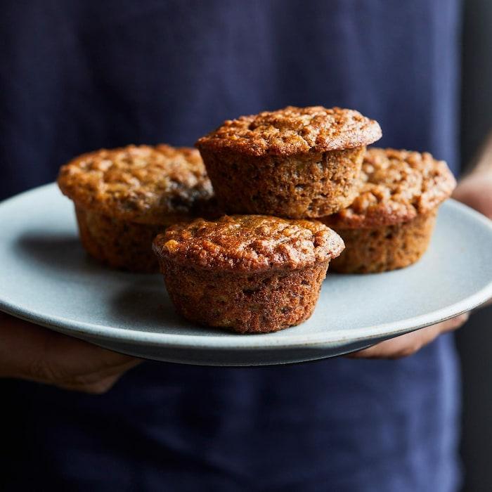 Une personne tient une assiette ronde contenant cinq muffins.