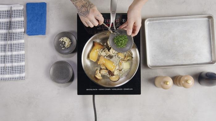 Sur une plaque de cuisson, des pleurotes cuisent dans une poêle.