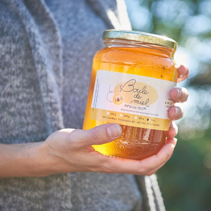 Une personne tient un pot de 1 kg de miel entre ses mains.