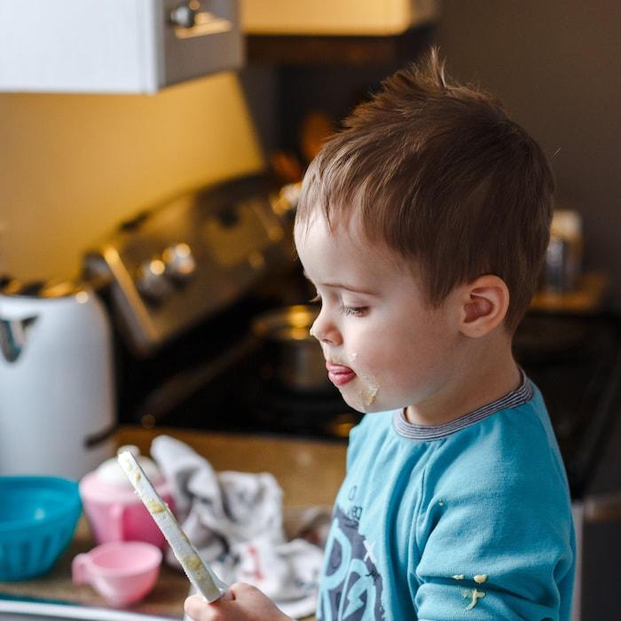Bambin dans une cuisine qui lèche un batteur.