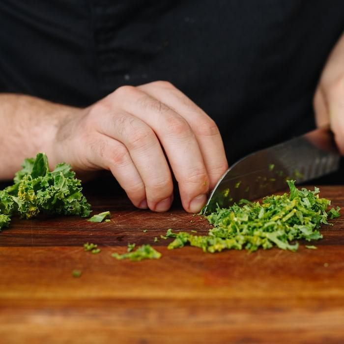 Personne qui coupe du kale (choux frisé) sur une planche de bois.
