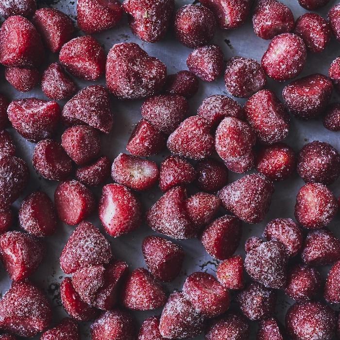 Des fraises mûres du Québec ont été congelées et elles sont déposées sur une plaque de cuisson.