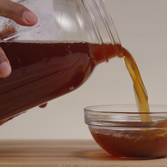 Une personne verse une boisson dans un petit bocal en verre.