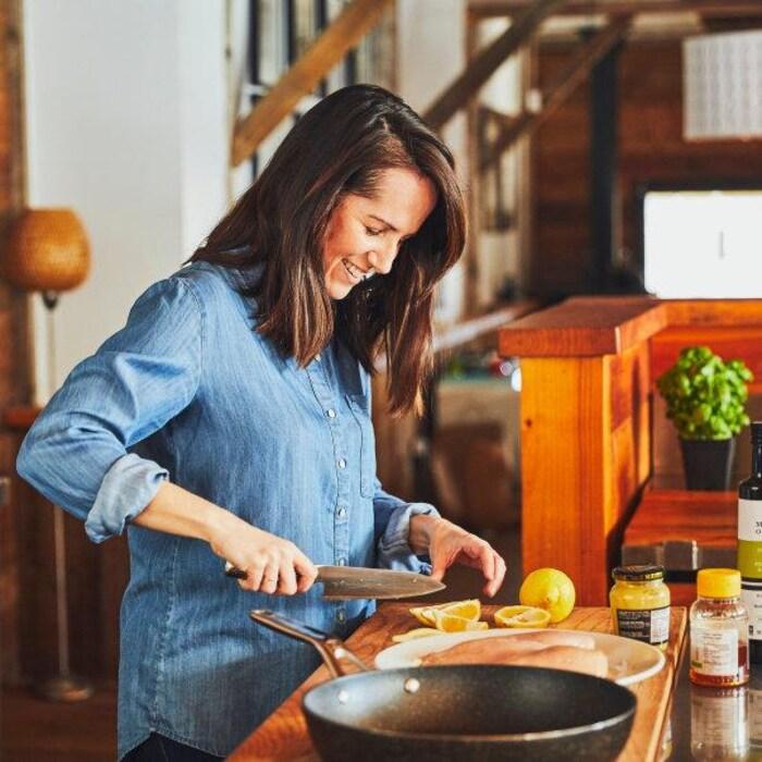 Geneviève O'Gleman coupe un citron. Elle est debout devant un plan de travail où on retrouve aussi une poêle, des poitrines de poulet, de la moutarde, du miel et de l'huile d'olive. Elle se trouve dans un chalet à l'ambiance chaleureuse.