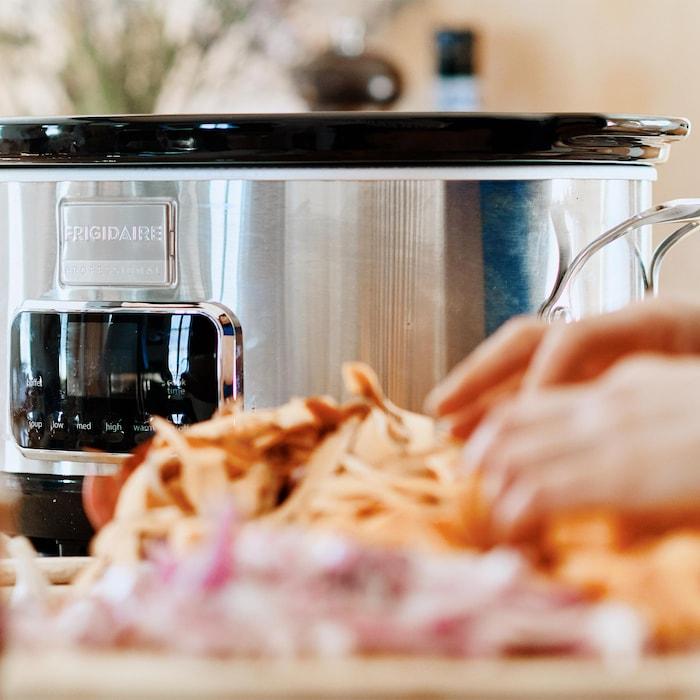 Une personne prépare des aliments pour les déposer dans la cuve de la mijoteuse.