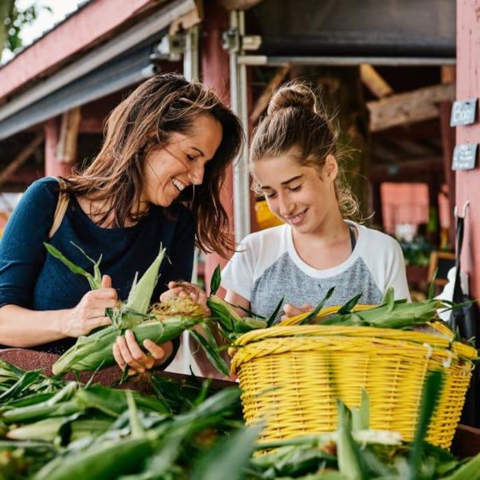 Geneviève O'Gleman choisit des épis de maïs dans un kiosk dans un marché.