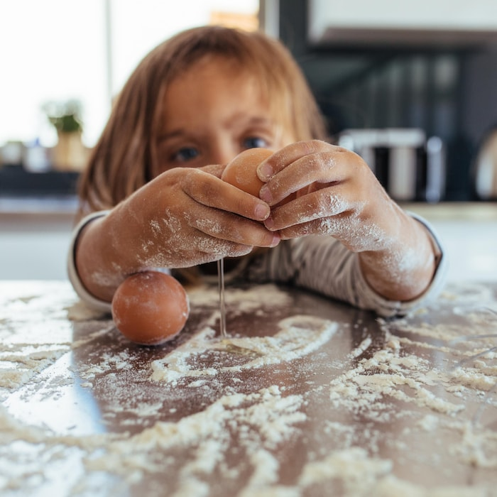 Enfant qui casse des oeufs sur un comptoir enfariné.