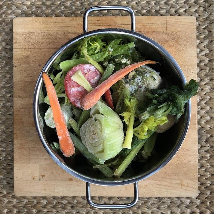 Casserole remplie de divers restes de légumes congelés.