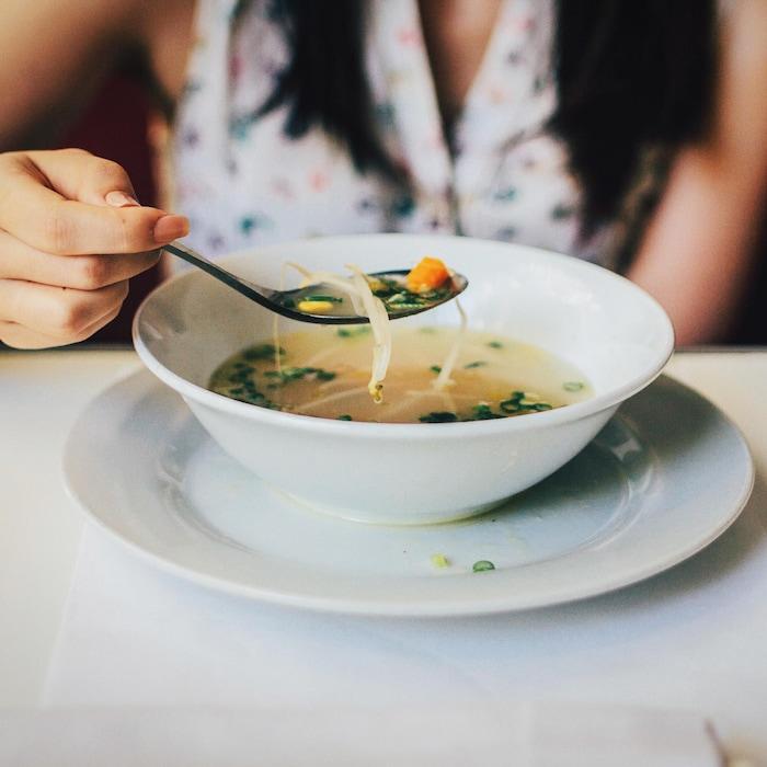 Assise sur une banquette, une personne tient une cuillère contenant un bouillon de légumes.