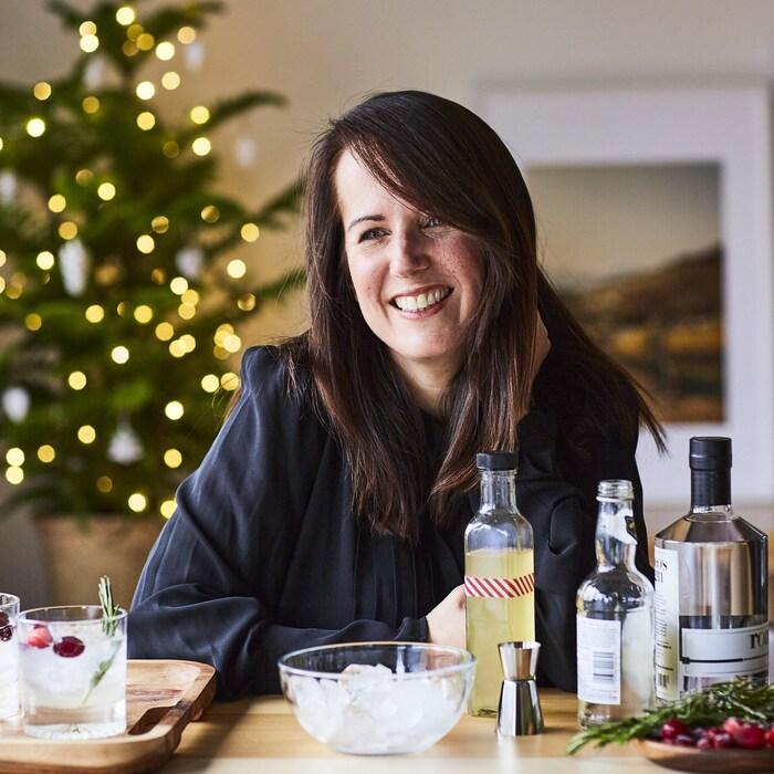 La nutritionniste Geneviève O'Gleman est assise, souriante, devant des drinks et des bouteilles de spiritueux. Elle est dans un décor de Noël.