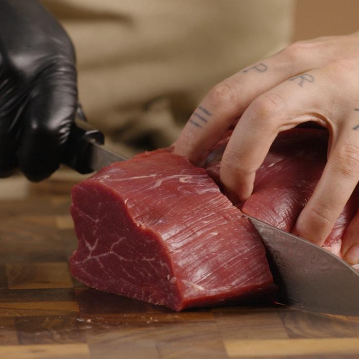 Couteau en main, une personne coupe un morceau du filet.