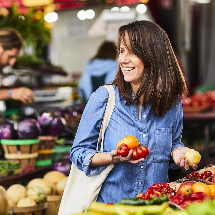 Geneviève O'Gleman dans un marché public extérieur qui achète des tomates.