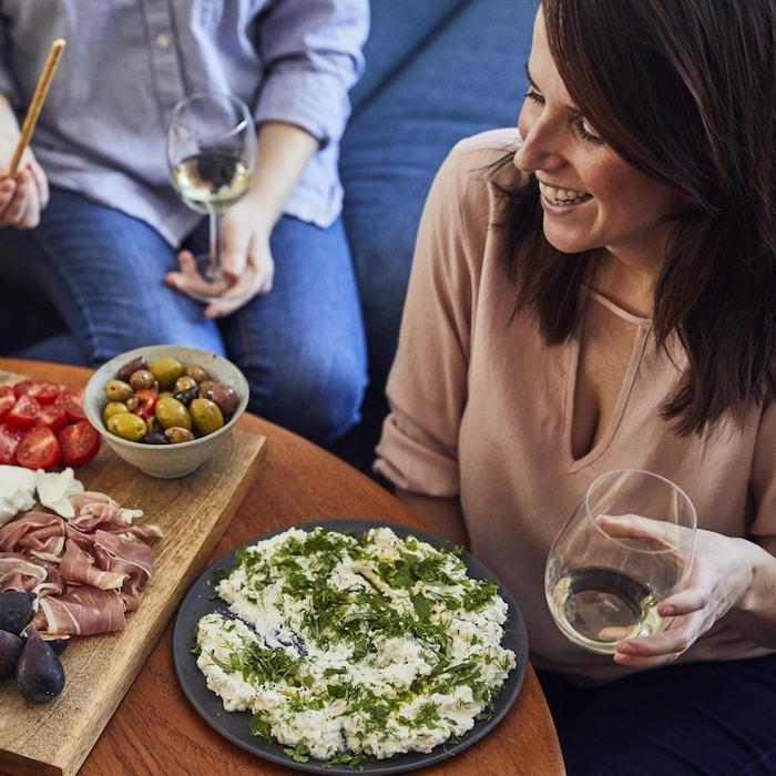 Geneviève O'Gleman avec des amis réunis autour d'une table avec des fromages, des charcuteries, des fruits, des légumes et du vin blanc.