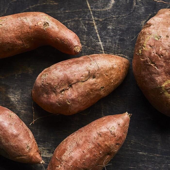 Cinq patates douces sur une table.